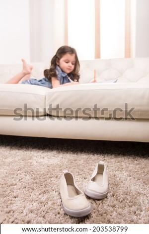 charming little girl writing in notebook. nice girl lying on white sofa - stock photo