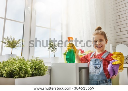 Charming little helper. Cute little child girl makes cleaning the house. Girl rubs dust. - stock photo