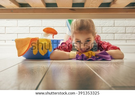 Charming little helper. Cute little child girl makes cleaning the house. Girl wipes the floor. - stock photo