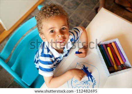 Charming Little Kid Looking Up and Playing with Crayons - stock photo