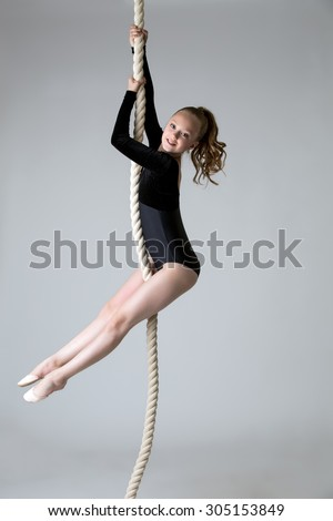 Charming little power gymnast climbs on rope - stock photo