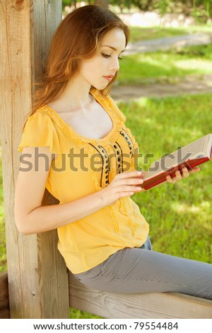 Charming long-haired girl reads book - stock photo