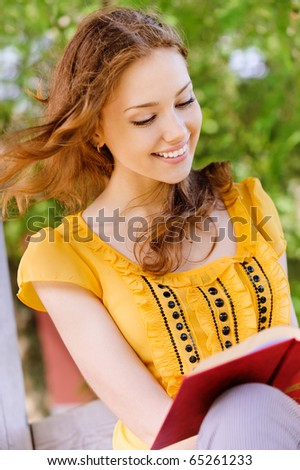 Charming long-haired girl-student reads red book - stock photo