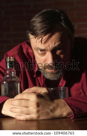 Charming man sits quietly at his home at the table - stock photo