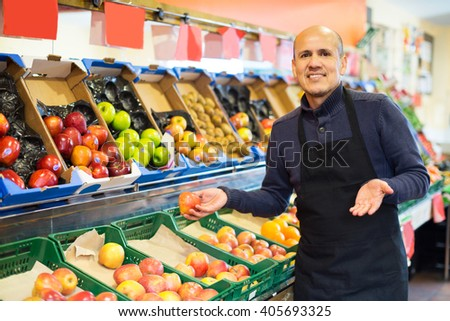 Charming mature salesman working in fruit section of supermarket