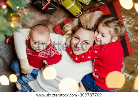 Charming mother blonde in white sweater hugs her daughter and toddler son in a red sweater lying on the floor near the Christmas tree and garlands in the house