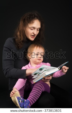 Charming mother showing images in a book to her cute little daughter over black background - stock photo