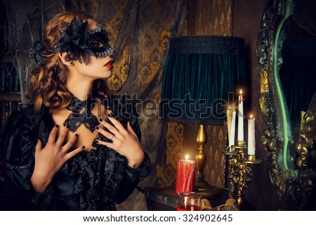 Charming mysterious girl in black mask and black medieval dress stands in a castle living room. Vampire. Halloween concept. Vintage style. - stock photo