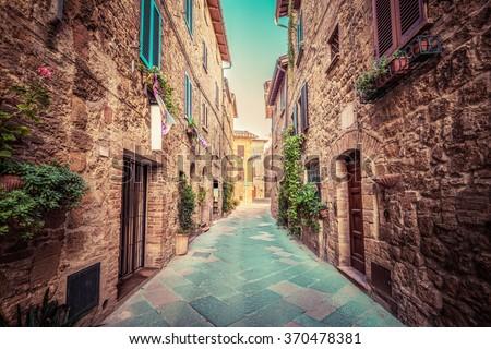 Charming narrow street in an old Italian town of Pienza. Tuscany, Italy. Vintage - stock photo