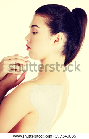 Charming nude woman enjoying a mud skin treatment on her back. - stock photo