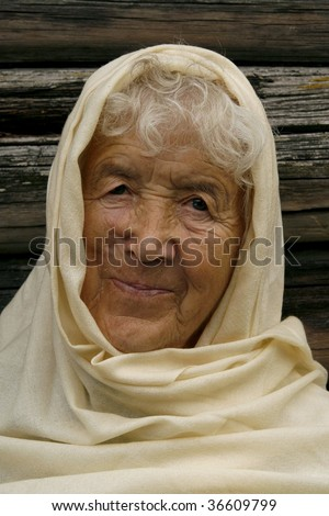 Charming old woman wrapped in a beige scarf. She is smiling and looking very happy.