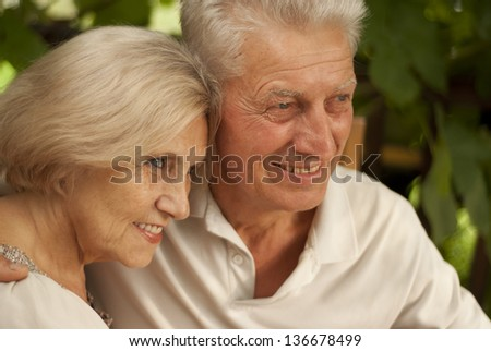 Charming older couple sitting at a table at home on the veranda - stock photo