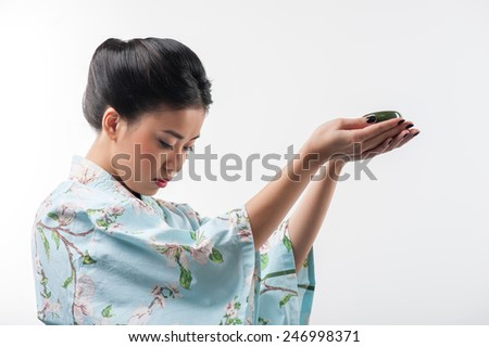 Charming oriental  woman. Side view portrait of young beautiful Japanese woman in traditional kimono holding out a cup of tea while standing against white background with copy space - stock photo
