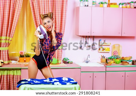 Charming pin-up girl ironing her dress and singing on a glamorous pink kitchen. Retro style. Fashion. - stock photo