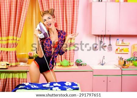 Charming pin-up girl ironing her dress on a glamorous pink kitchen. Retro style. Fashion. - stock photo
