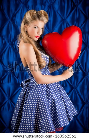 Charming pin-up woman with retro hairstyle and make-up holding red balloon in the shape of heart. - stock photo