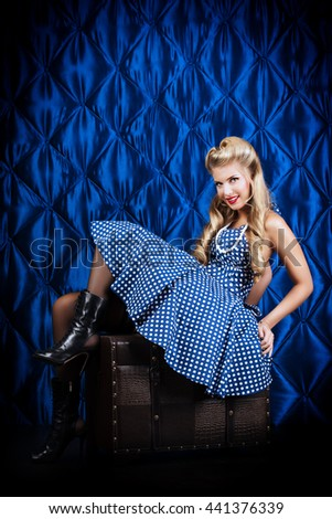 Charming pin-up woman with retro hairstyle and make-up sitting in the armchair over vintage background.