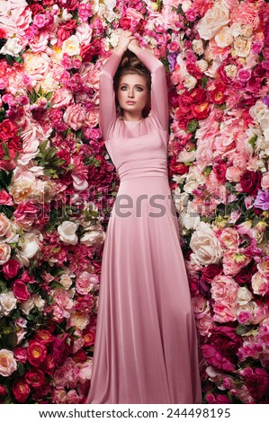 Charming portrait of young beautiful girl in rosy skin-tight gown with dark smoky eyes and natural lipstick, on flowered background made of peony - stock photo