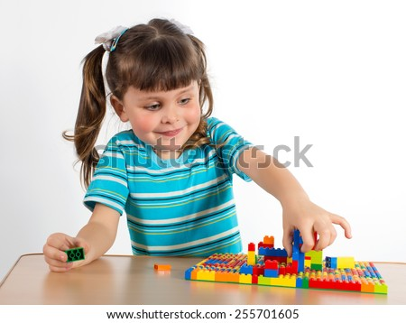 Charming preschooler playing with small constructor. Little girl playing with connecting toy cubes  - stock photo