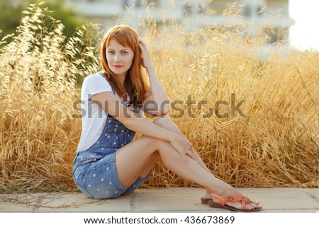 Charming red-haired girl in denim overalls sitting on a background of yellow dry grass at sunset in summer - stock photo