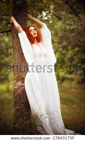 Charming redhead woman wearing white dress stands near the tree - stock photo
