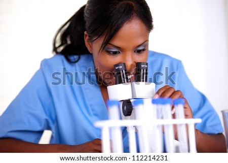 Charming scientific female using a microscope at laboratory