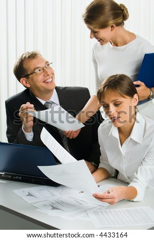 Charming secretary is showing important document  to her boss in the office