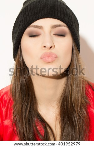 Charming seduction. Close up shot of a gorgeous hipster female blowing a kiss with her closed eyes. - stock photo