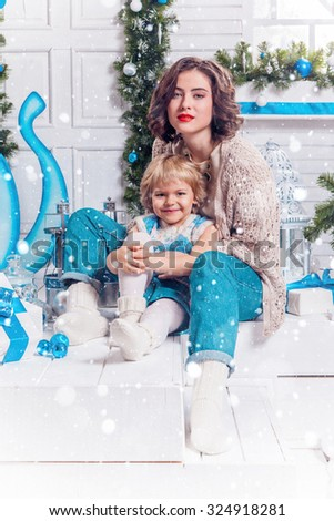 Charming sexy woman with red lipstick and her daughter in a knitted sweater and jeans sitting on the porch with gifts in hand, it is snowing, picture with depth of field - stock photo