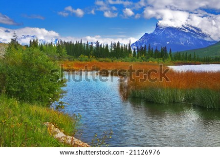 Charming shallow lake with small islands on a background of the Rocky mountains covered by a snow - stock photo