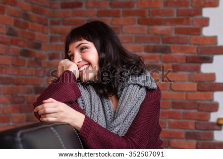 Charming shy young woman in knitted gray scarf sitting on leather sofa and laughing over brick wall background - stock photo