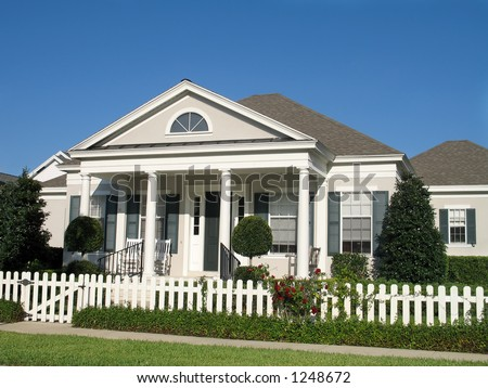 charming small town America cottage with picket fence around a lush lawn - stock photo