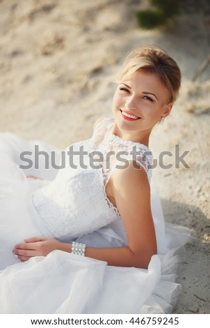 Charming smile of the bride on the sand - stock photo