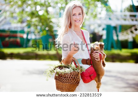 Charming smiling blonde girl holding a basket and a dog - stock photo
