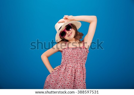 Charming smiling little girl in hat, sundress and sunglasses standing and showing peace sign over blue background - stock photo