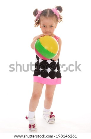 Charming smiling little girl with the ball in his hands standing on a white background - stock photo