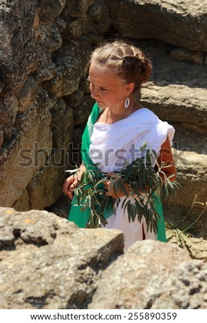 Charming smiling young girl in a Greek tunic holds an olive sprig on the background of the archaeological site of the ancient city of Nymphaeum in the village Geroevskoe, Kerch, Russia - stock photo