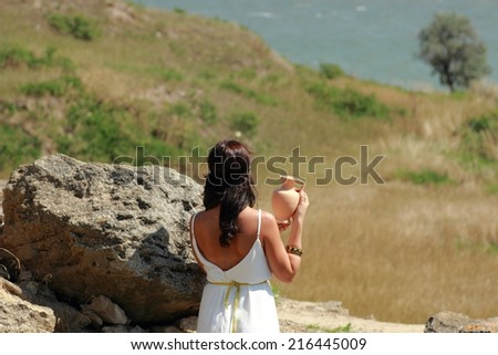 Charming smiling young woman in a Greek dress holding the old amphora on the background of the excavations of the ancient city of Nymphaeum - stock photo