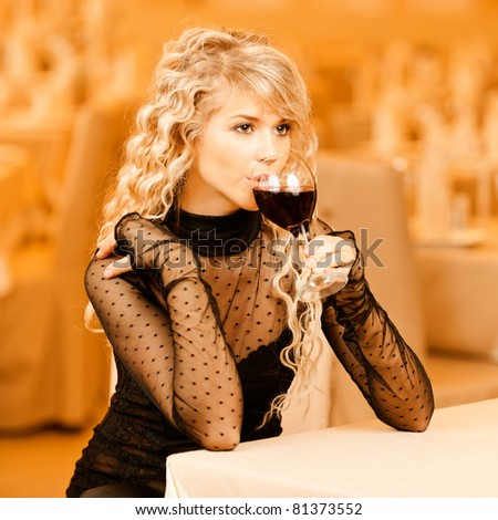 Charming smiling young woman in black clothes drink from red wine glass sits at magnificent restaurant. - stock photo