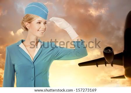 Charming Stewardess Dressed In Blue Uniform On Sky Background - stock photo