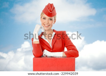 Charming Stewardess Dressed In Red Uniform And Suitcase. Sky With Clouds Background. - stock photo