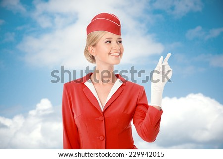 Charming Stewardess Dressed In Red Uniform Pointing The Finger. Sky With Clouds Background. - stock photo