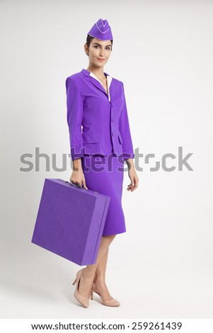 Charming Stewardess Dressed In Violet Uniform And Suitcase - stock photo