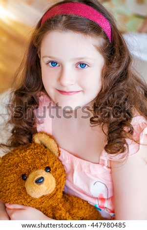 Charming, sweet, beautiful little girl in nightgown, hugging teddy bear sitting on bed, on the background of cozy room.  Happy childhood. background, closeup, macro
