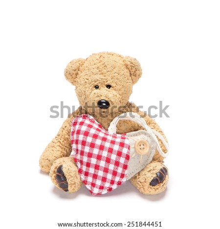 Charming teddy bear holding fabric heart in paws on white background - stock photo