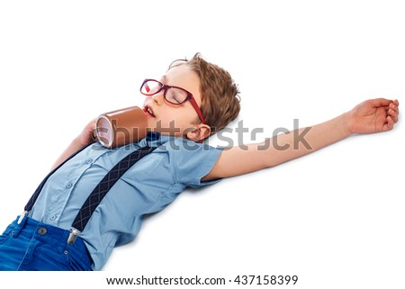 Charming tired boy in glasses lying on the floor with cup of tea, coffee or juice. He is sleeping. Isolated on a white background. - stock photo