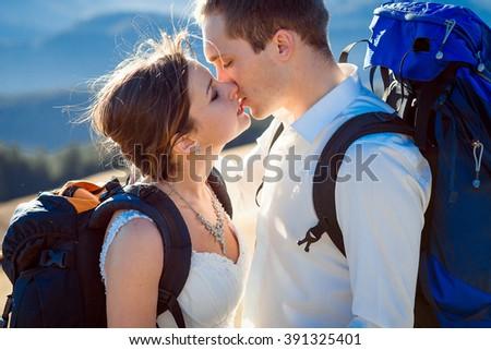 Charming tourist wedding couple kissing on the mountain peak close up - stock photo