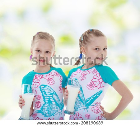Charming twin sisters with glasses of milk.kindergarten, the concept of childhood and joy, teens - stock photo