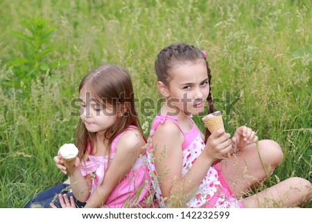 Charming two young girls eat ice cream and lie on the grass outdoors - stock photo