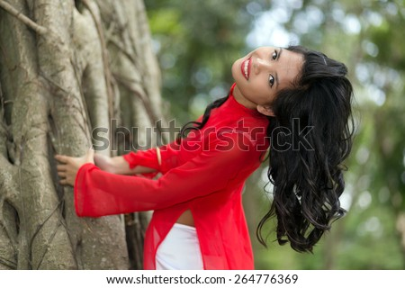 Charming Vietnamese woman bending over a large fig tree in a park, Vietnam - stock photo